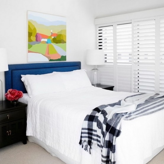 a neutral bedroom with a touch of color - a navy headboard, a black nightstand, a colorful artwork, looks larger and bolder