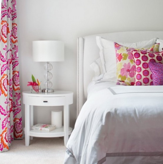 a small bedroom decorated only in white and with just a splash of bright colors - pillows and curtains - looks bold and cool