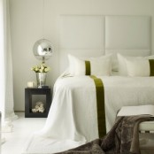 an oversized headboard with horizontal upholstered panels and mirror pendant lamps used for enlarging the space