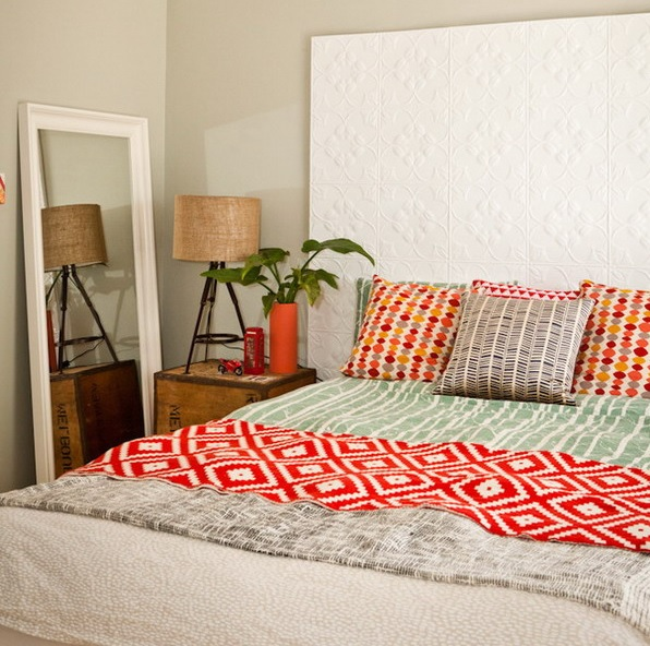 an extended patterned headboard done with panels is a lovely idea for a small space, bright bedding adds to the room