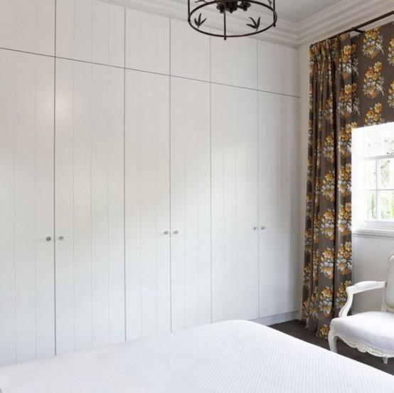 a small bedroom with white on white decor and a contrasting floor and dark floral curtains for a bold contrast