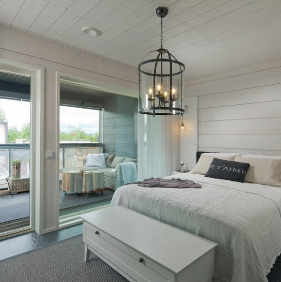 a neutral farmhouse bedroom with horizontal beadboards covering the walls and ceiling to visually expand the bedroom