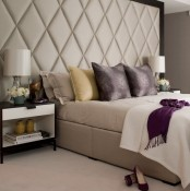 a neutral bedroom with an oversized extended upholstered headboard looks luxurious and very large
