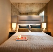 horizontal panels and a vintage mirror over the bed make the small bedroom look larger and cooler