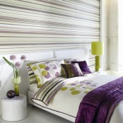 an accent wall with horizontal stripes makes the bedroom look wider and bigger at the same time