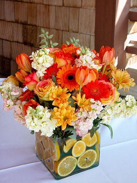 A seasonal arrangement of ornamental flowers in vibrant colors takes center stage on the dinner table.