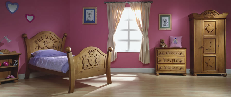 a mauve Princess themed kid's room with carved wooden furniture and touches of blue