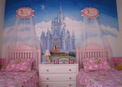 a princess castle-inspired girl's bedroom with a castle artwork and pink beds with canopies is a very dreamy space