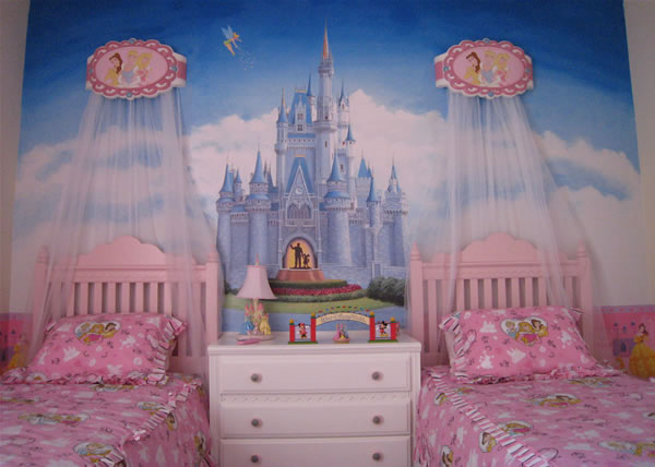 a princess castle inspired girl's bedroom with a castle artwork and pink beds with canopies is a very dreamy space