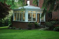 a conservatory externsion that features a cool pyramid-shaped glass roof