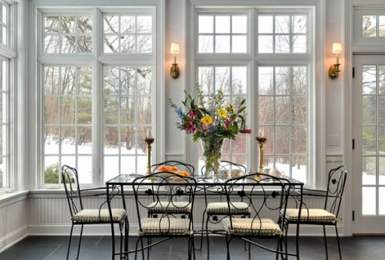 a dining room surrounded by windows - Sunroom Dining Room