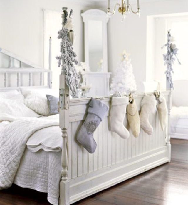 a neutral Christmas bedroom with cozy bedding, faux fur pillows and blankets and stockings and snowy evergreens