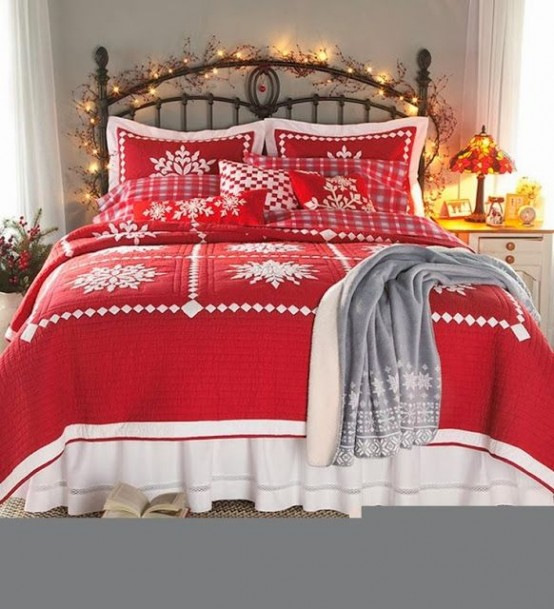 a Christmas bedroom with red and white bedding, a grey plaid blanket and lights covering the headboard