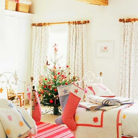 a Christmas bedroom with a Christmas tree and colorful pompoms, bright bedding and star printed blankets