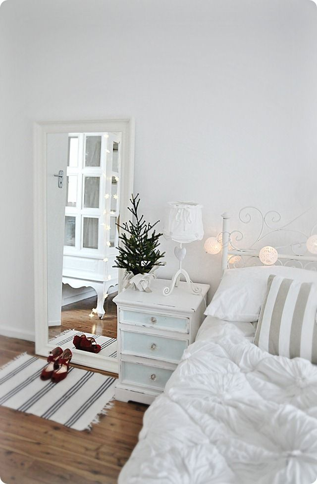a mini Christmas tree, lights and stars for a neutral bedroom that feels like holidays