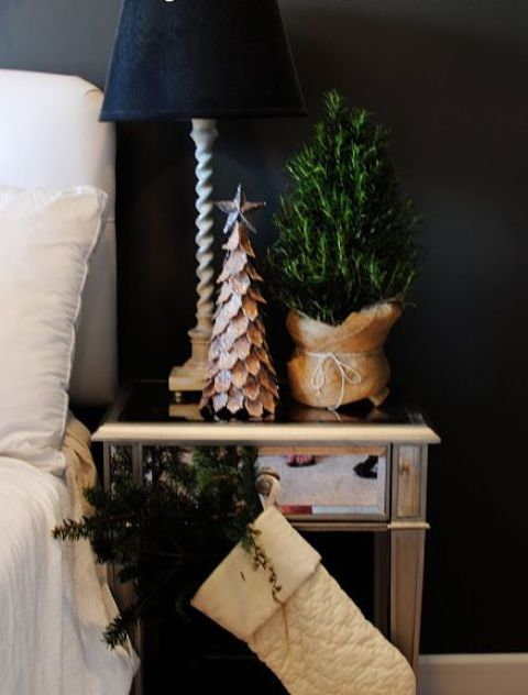 a white stocking with evergreens, a mini tree in burlap and a tree made of cardboard to bring a holiday feel