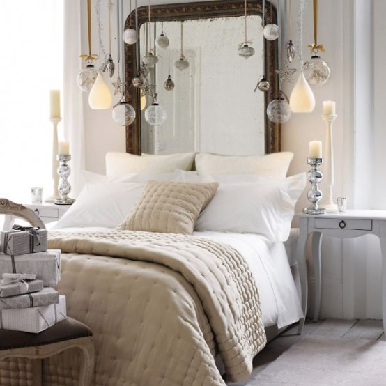 a neutral Christmas bedroom with a vintage chair with a gift box stack and lots of ornaments hanging over the bed