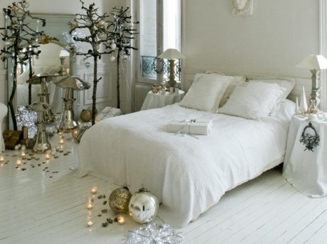 a white Christmas bedroom with quirky trees decorated with sheer and silver ornaments, candles, lamps and oversized ornaments on the floor