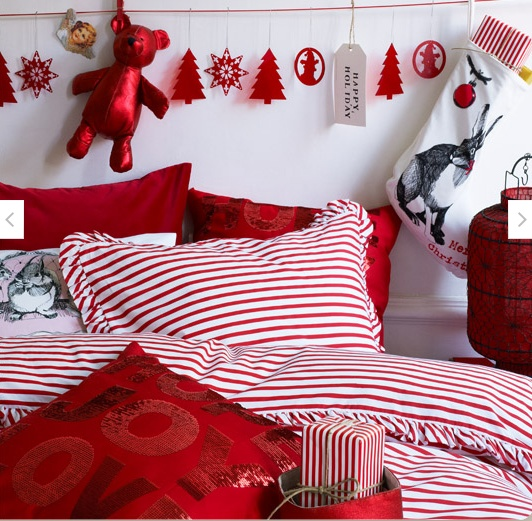 a bright red and white Christmas bedroom with a paper bunting, red and striped bedding plus a holiday pillow
