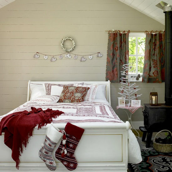 a wooden ornament bunting, red and white bedding and a mini white Christmas tree with red ornaments