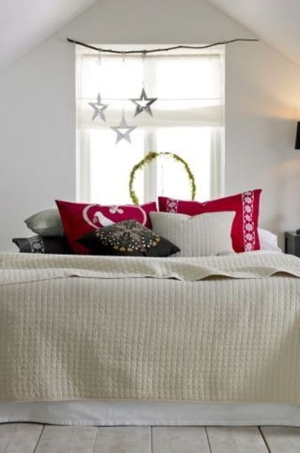 stars over the bed and red Christmas pillows immediately bring a holiday feel to the space