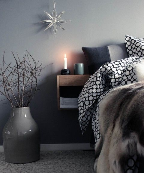 some faux fur, a star ornament and branches in a vase for a grey Christmas bedroom