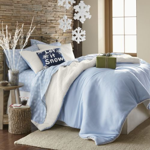 a neutral bedroom decorated with frosted lights in a vase, snowflke hangings and a blue bedding set inspired by Christmas