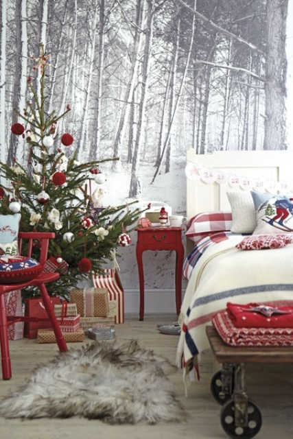 a bright festive bedroom with a mini Christmas tree with red and white ornaments, red furniture, a bench with red blankets and plaid bedding