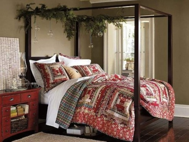 a Christmas bedroom with bright quilted bedding, evergreens and clear bubble ornaments hanging on the bed frame