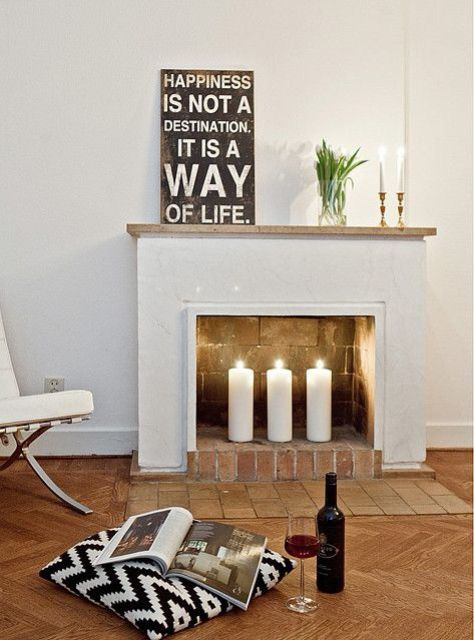 a minimalist look with three large pillar candles and some candles on the mantel