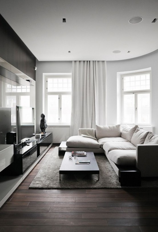 a monochromatic minimalist living room with dark stained furniture and a floor, white walls, curtains and a sofa