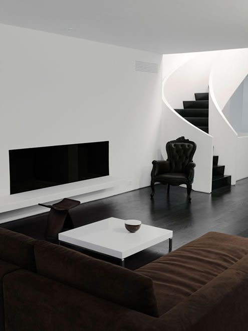 a minimalist black and white living room with elegant furniture and a dark brown sectional sofa
