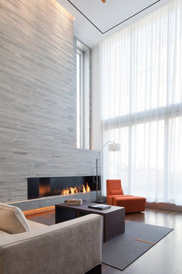 a double height minimalist living room with a wood clad fireplace wall, contemporary furniture and a large window for more natural light