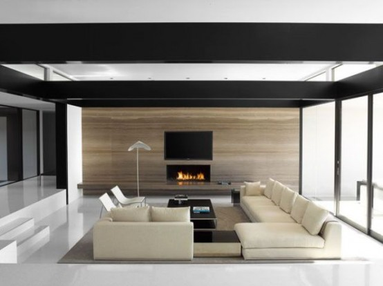 a minimalist living room with a conversation pit, contemporary furniture, a fireplace and a dark framed ceiling