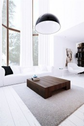 a white minimalist living room with double height windows, a white sofa, a dark stained coffee table and a pendant lamp