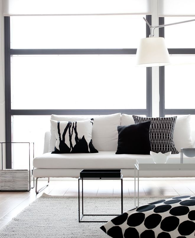 a minimalist black and white living room with a stylish white couch, printed black and white pillows plus coffee tables
