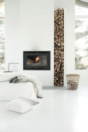 a minimalist all-white living room with a fireplace and a firewood storage space, a white sofa and large windows for more light