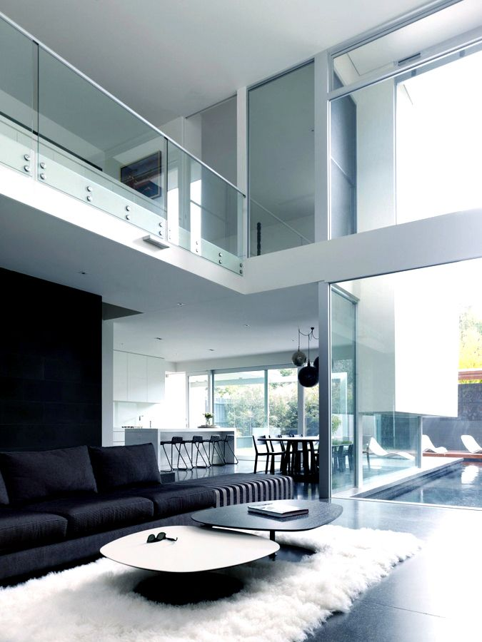 a stylsh minimalist monochromatic living room with a fur rug and laconic coffee tables