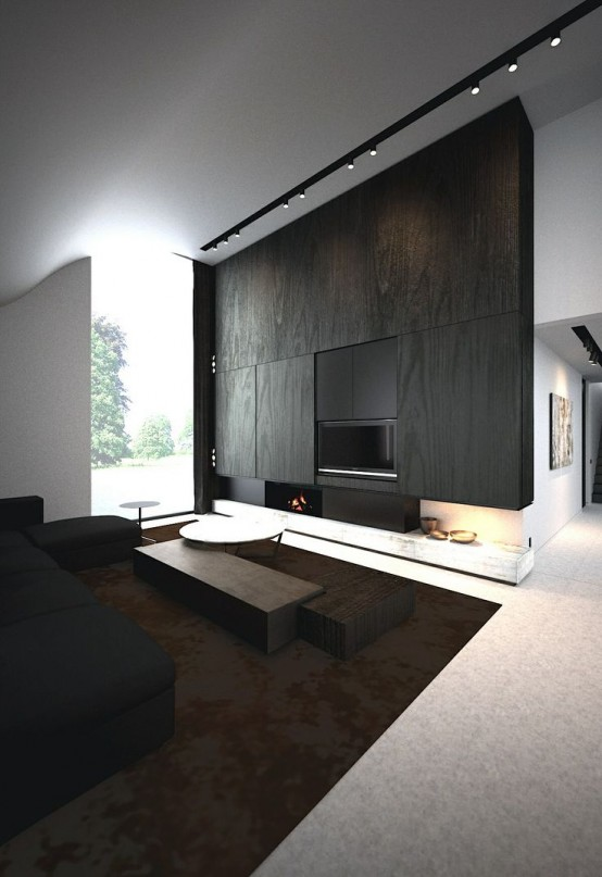 a minimalist living room with a wood clad wall and fireplace, a black sofa and dark stained furniture