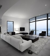 an elegant black and white minimalist living room with a view, chic furniture and a furry rug on the floor
