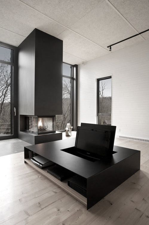 a minimalist living room with large windows for views and natural light, a black hearth and a black coffee table with a hidden TV