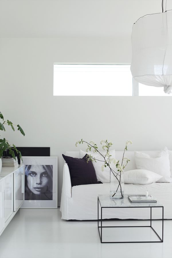 a pure white minimalist living room with a small window, a paper lamp and touches of black for more drama