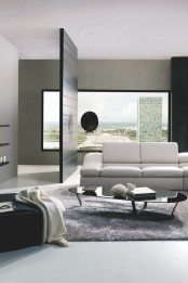 an elegant minimalist living room with a view, a white sofa, black furniture and a grey rug