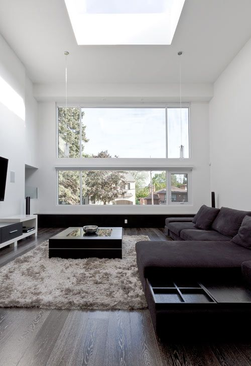 a chic and welcoming minimalist living room with dark furniture, a fluffy rug, a TV and a large window plus a skylight
