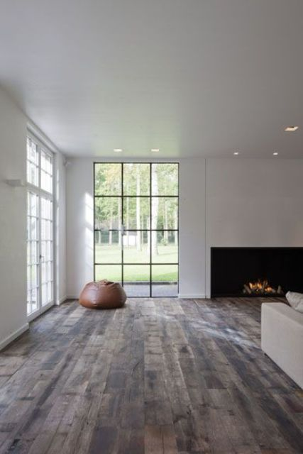 a minimalist liivng room with a fireplace, a white sofa and large windows that offer much natural light