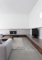 a chic grey and white minimalist living room with a fireplace, firewood storage, grey furniture and a fluffy rug