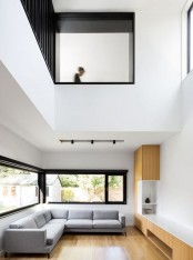 a minimalist double-height living room with a grey sectional sofa, neutral wooden furniture, windows to flood the space with light