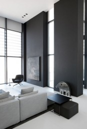 a minimalist living room with black walls, a grey sectional sofa, black furniture items and much natural light