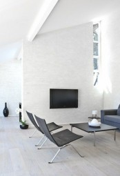 a white minimalist living room with a TV, windows, black and grey furniture that looks comfortable and cozy
