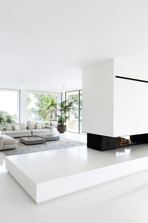 a minimalist and light-filled living room with a fireplace and firewood storage, a grey sectional sofa and panoramic windows